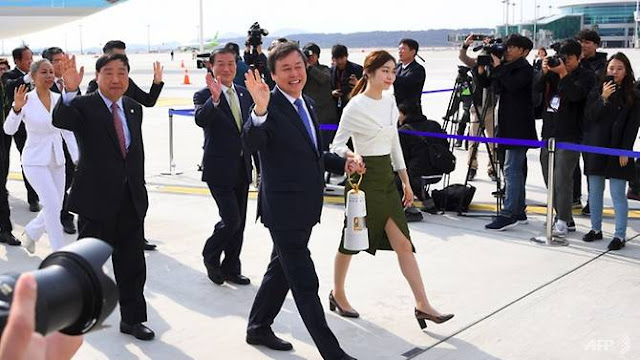 South Korea's Culture, Sports and Tourism Minister Do Jong-whan (C) and former figure skating champion Yuna Kim (R) carry the Olympic flame upon its arrival at Incheon International Airport, west of Seoul, on Nov 1, 2017. (Photo: AFP/ Jung Yeon-je)