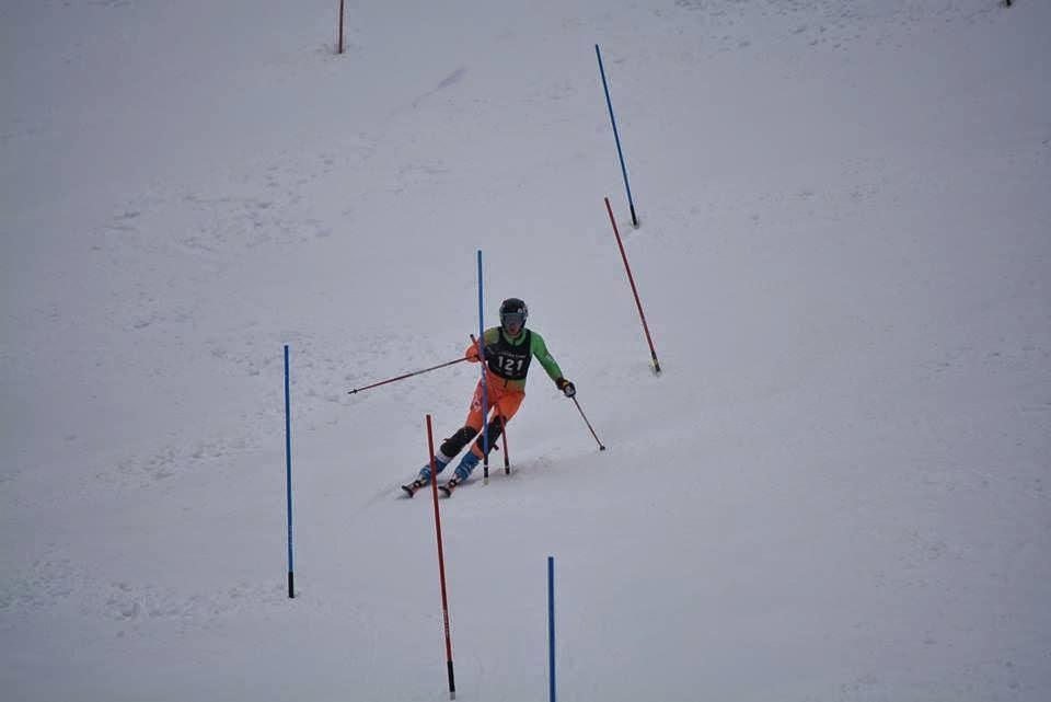Skier dodging poles downhill