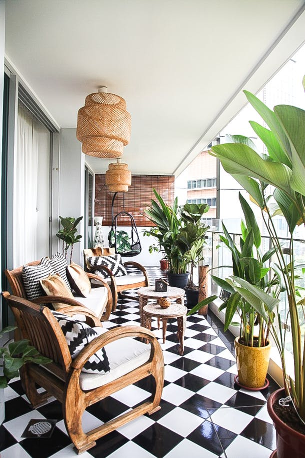 Outside the living room, a beautiful covered terrace acts as a miniature backyard with verdant plants.