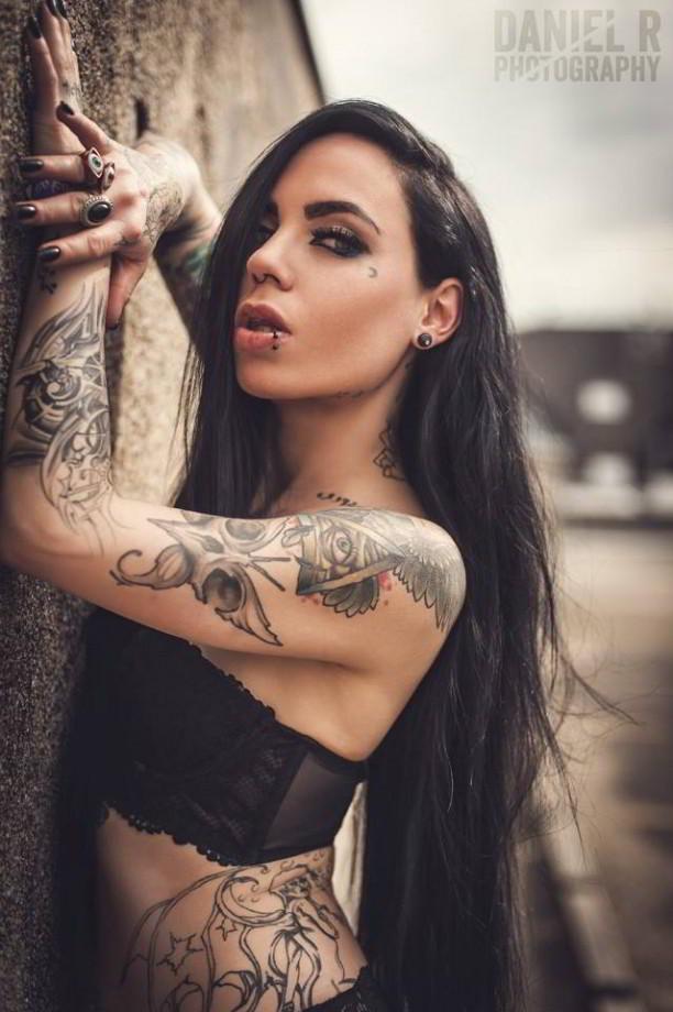Chica morena apoyada en un muro, lleva tatuaje del ojo que todo lo ve en su brazo
