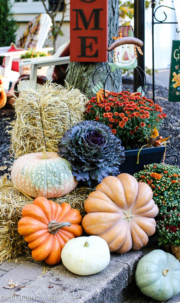 Fall decor for outdoors with heirloom pumpkins, hay bales and mums