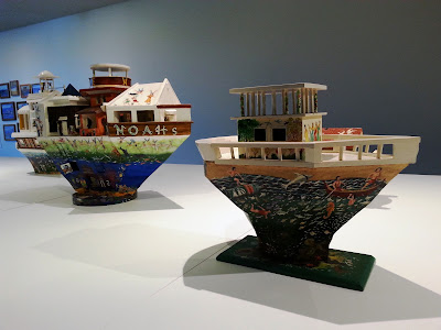 Two miniature wooden painted artist's arks on display in a gallery.