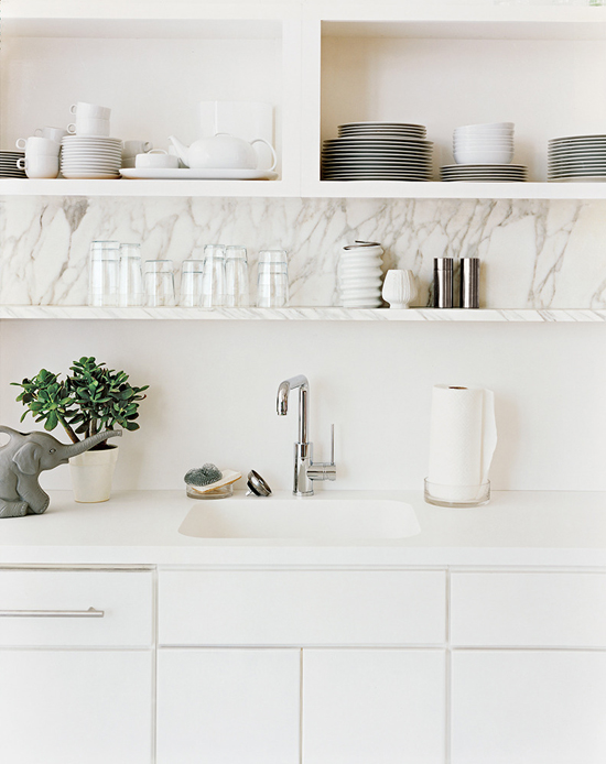 Interiors: Open marble shelving and sleek white cabinetry. Photo via Domino.