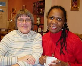An older white woman and younger black woman share a home, offering the benefits of diversity.
