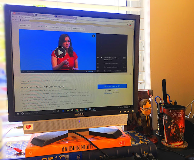 Amy Schmittauer is giving a class on vlogging on my computer screen. You can see my Star Wars cup and Dwight bobble head; that's how you know I mean business.