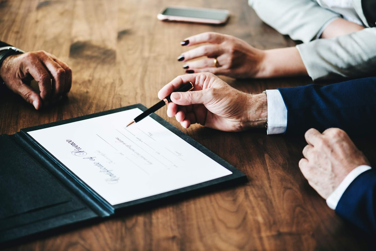 lawyer signing a document with a client