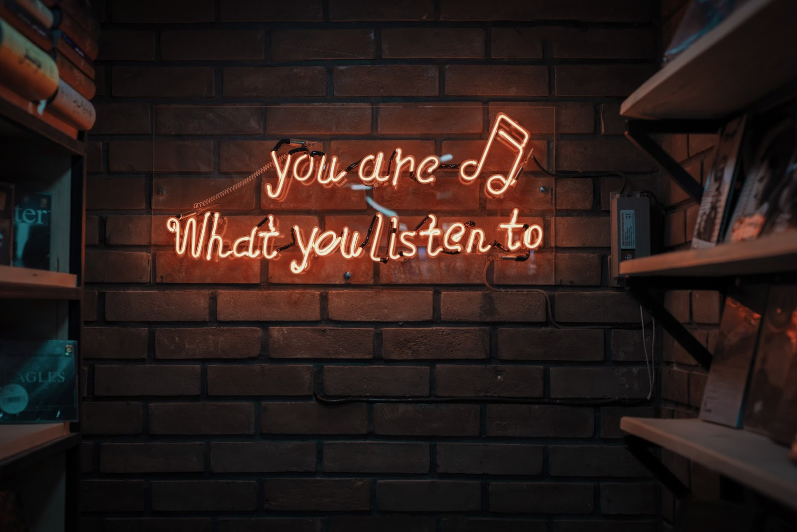 "neon sign that says ""you are what you listen to"""