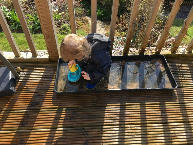7 Easy Ways To Amuse A Toddler in The Garden. Toddler in tray of water