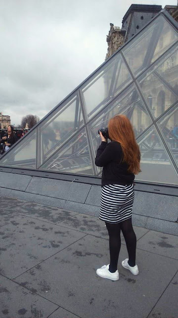 Me taking photos in front of the glass pyramid at the Louvre, Paris