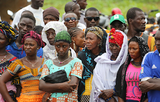 Families wait to collect sacks of food at a food distribution center in Kindia, Guinea on June 15, 2015.