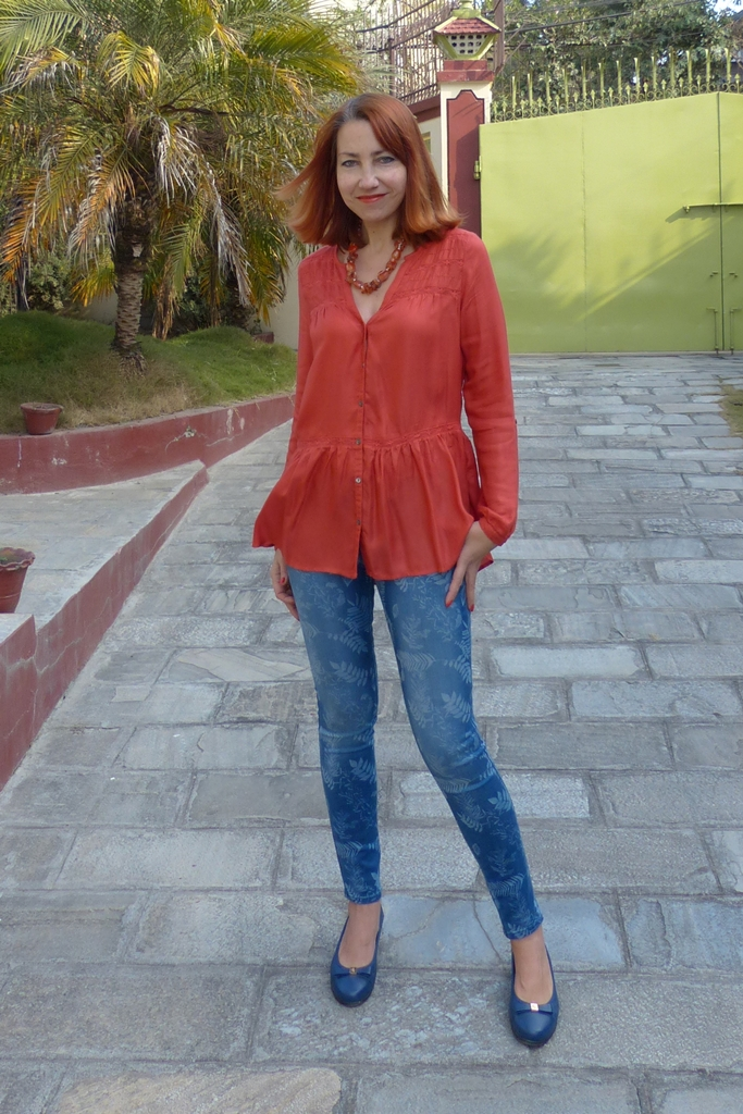 Printed skinny jeans and orange top, blue flats and cornelian necklace