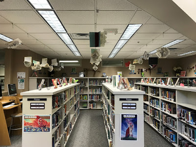Weeded Art books hang from library ceiling