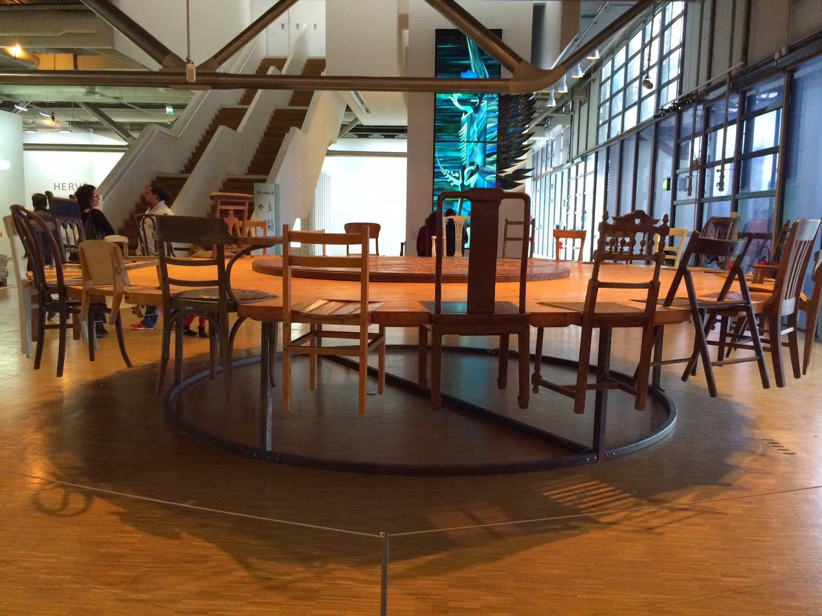Pic of wooden rounded table artwork with different sized chairs embedded in it