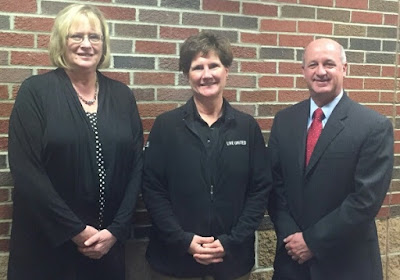 Cathy Whalen wearing a black jacket presenting United Way Preschool Grant to Susan Congrove in a black dress and Jerry Mowery wearing a black suit, white shirt and red tie