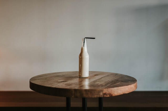 Glass-Bottle-Filled-With-Black-Straw-on-Brown-Wooden-Table