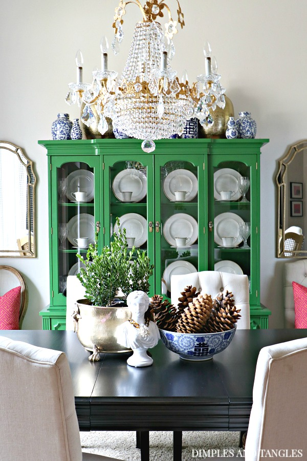 green china cabinet, vintage crystal chandelier, blue and white, sugar pinecones, dark stained vintage table, tufted upholstered chairs