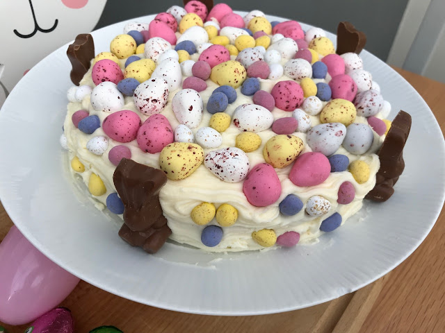 A cake covered in frosting, mini eggs and chocolate bunnies