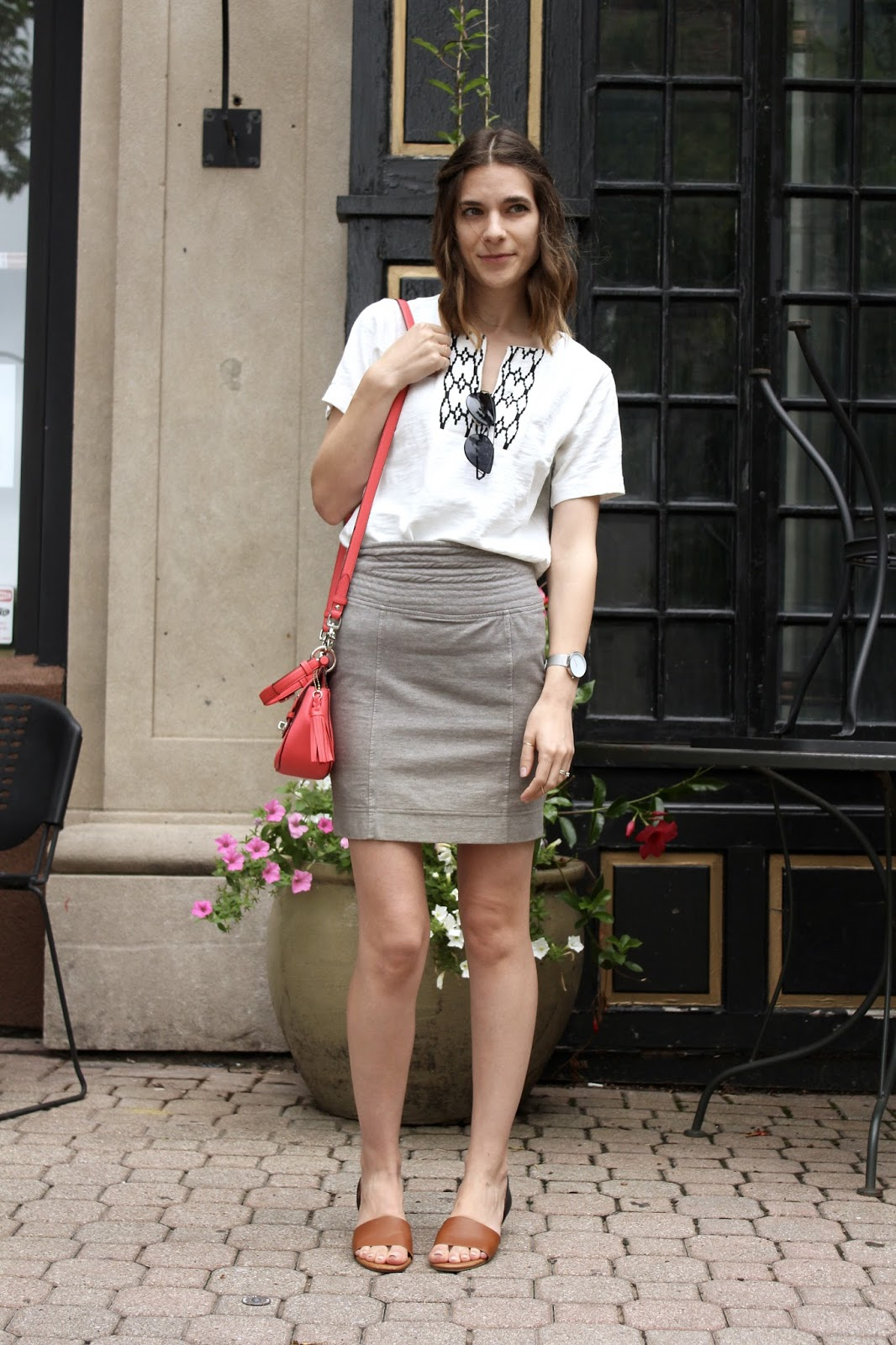 white t-shirt paired with a high waisted gray pencil skirt