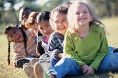 Seis niños sentados en el césped
