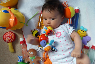 Baby on mat with lots of toys