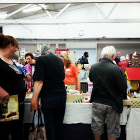 People at a miniatures show, browsing a stall with boxes of stock.
