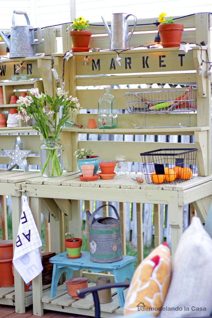 green potting benches with lots of pots, watering cans, flowers and lights