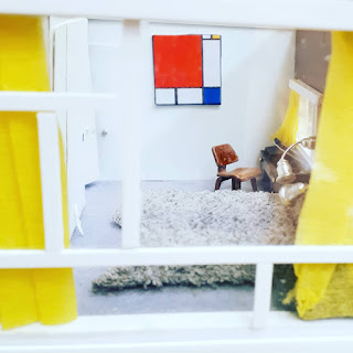 View through the window of a 1/48-scale mid-century modern house, showing a bedroom in white with accents of bright colour.