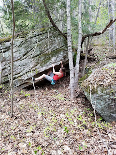 girl climbs boulder in woods