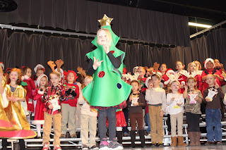 Child dressed as a Christmas tree with students behind her