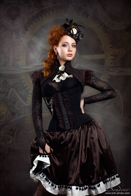 Steampunk redhead wearing lace blouse, corset, feathers, fascinator. Wome's steampunk clothing and costumes