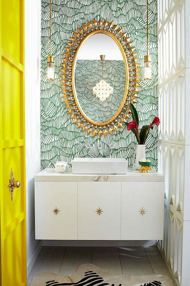 Espejo forma sol con detalles dorados sobre pared con papel pintado en verde