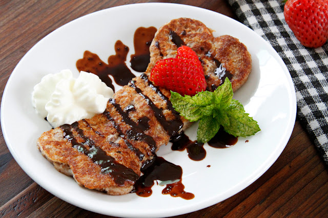 Homemade bone shaped dog pancake with carob sauce, whipped cream, strawberry hearts, and fresh mint