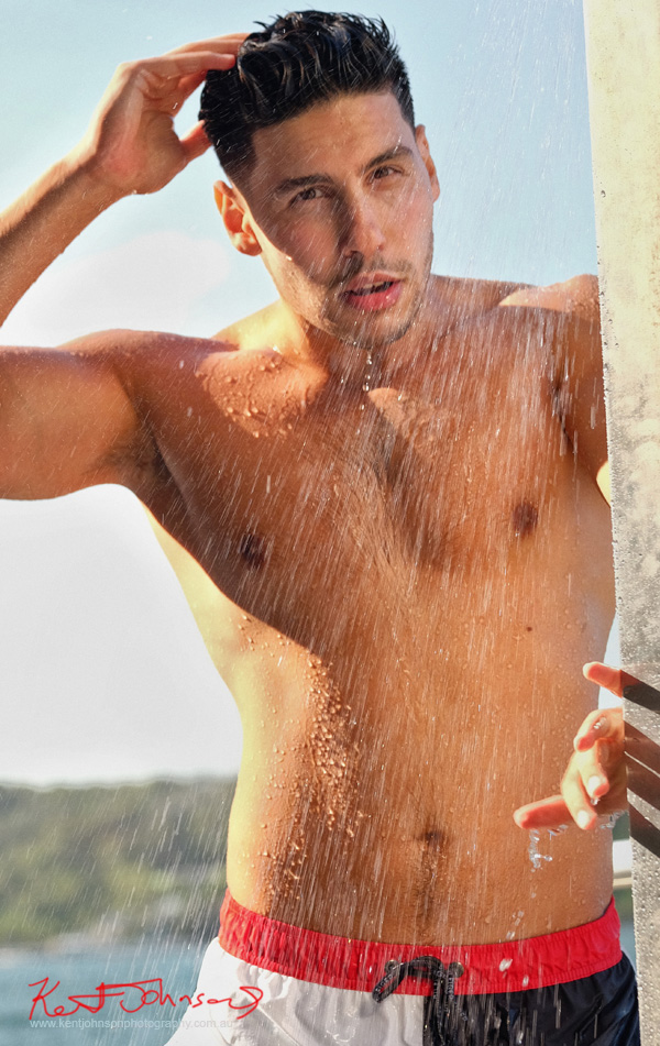 Action shot with shower spray and harbour and parkland in background. Male modelling portfolio shot on Location in Sydney Australia by Kent Johnson.