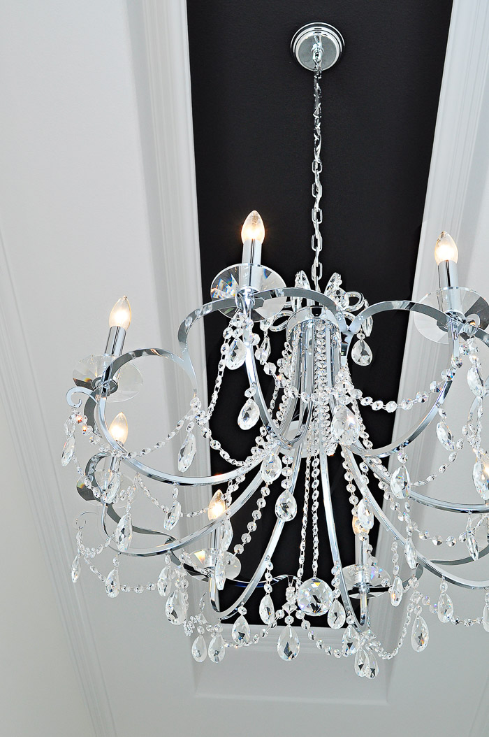 Simple  Light Chrome and Crystal Chandelier by Crystorama in a black and white foyer