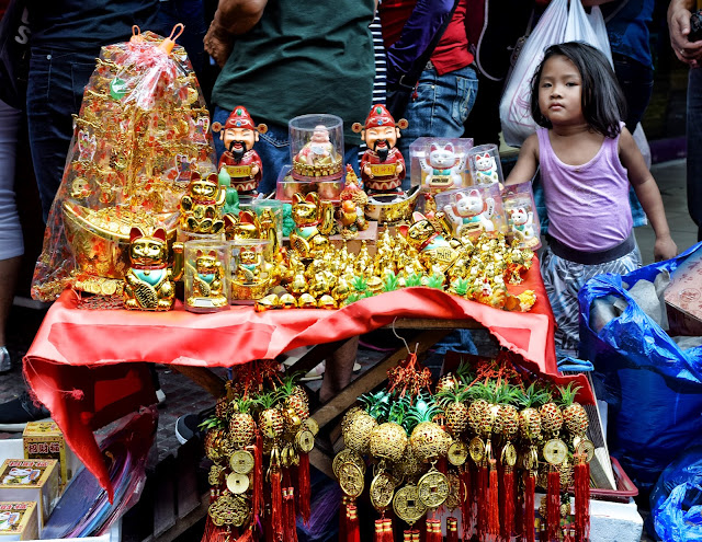 A young girl looks at me as I take a shot of her mother's merchandise