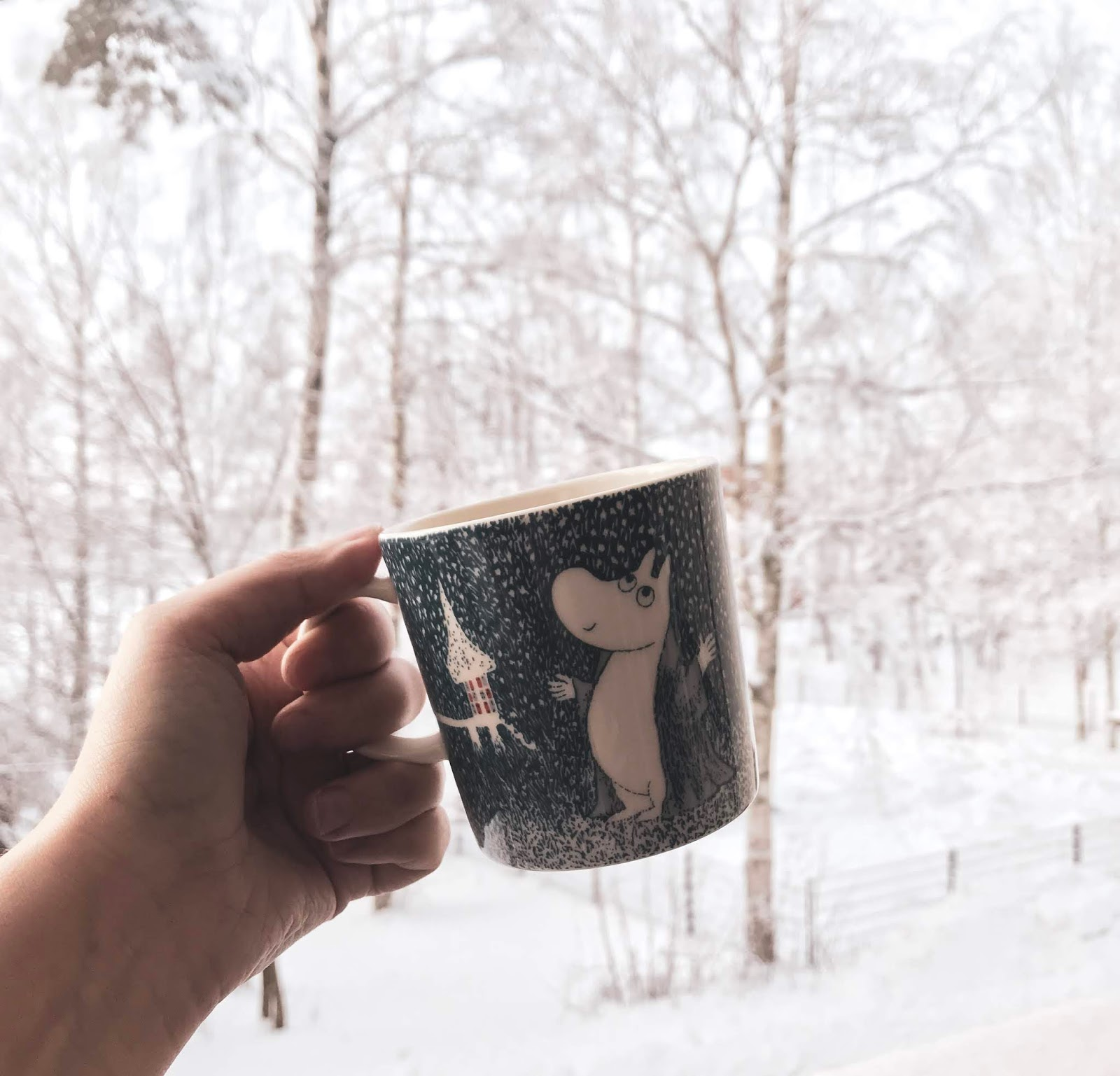 a hand holding the wintery moomin mug in a wintery and snowy background