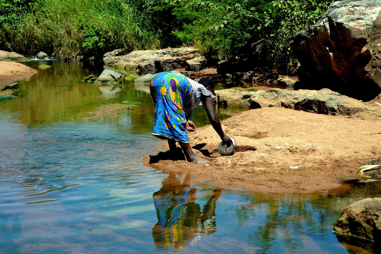 woman collecting water in africa at a water source