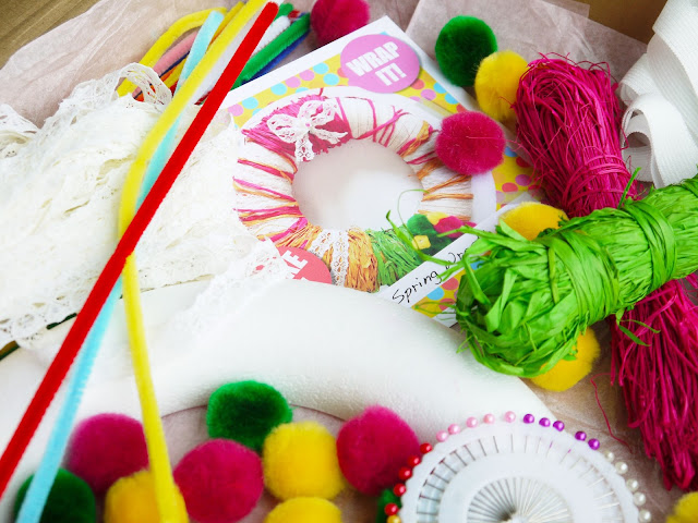 a selection of pink, yellow, and green pom poms, pipe cleaners, raffia string, white lace, and a wheel of pins
