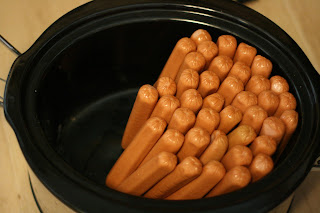 a lot of hot dogs in a crockpot for a party