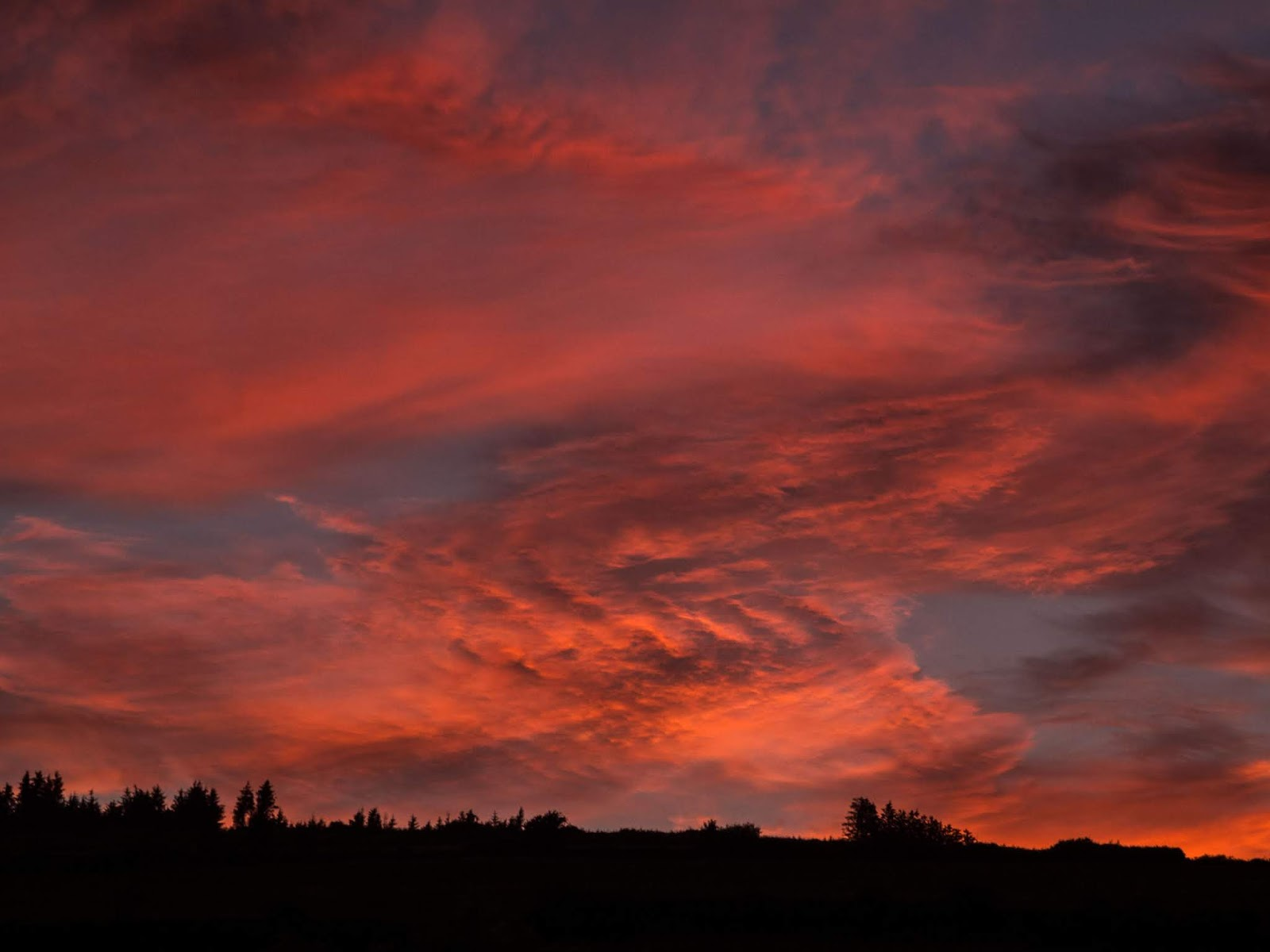 Red cirrostratus clouds at sunset over a mountain side in Co.Cork.