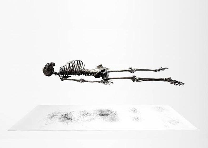 Un esqueleto del grafito de tamaño natural vibra para dibujarse a sí mismo en el olvido