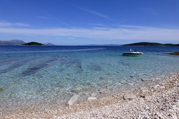 Meer mit klarem Wasser und Sportboot