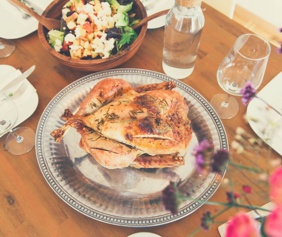 A cooked chicken sits on a silver platter, with a bowl of salad nearby on a wooden table. Teaching our children to cook is so important.