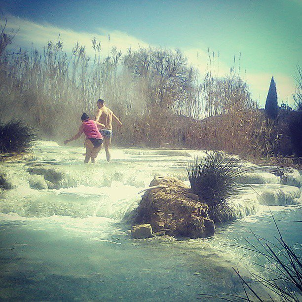 A couple wading through the natural pools of Saturnia
