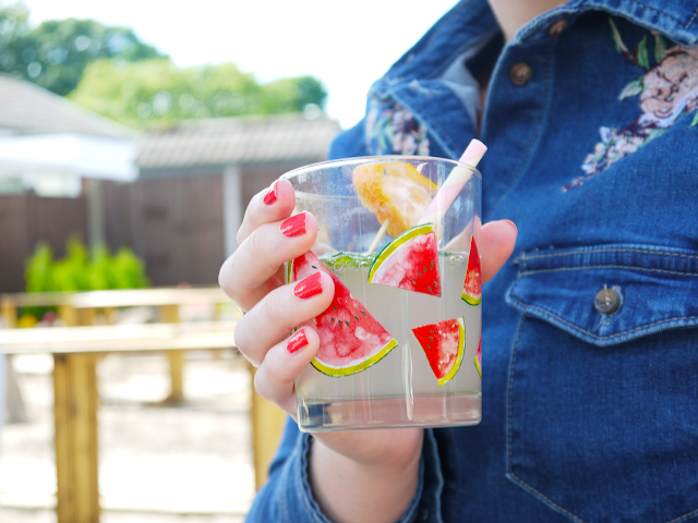 holding a glass of franklin and sons lemonade in watermelon print glass