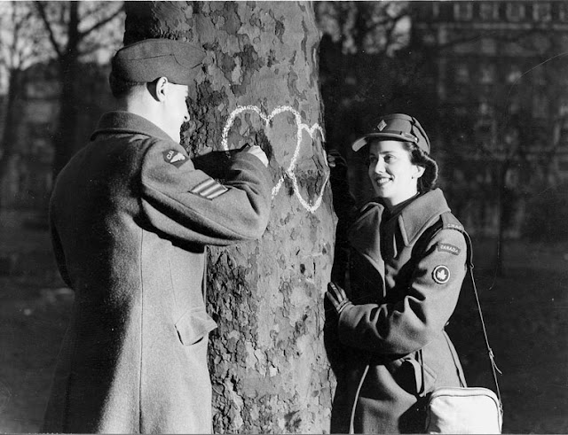 Young couple chalking hearts onto a tree. Valentine's Day, 1944. The Galt Museum & Archives