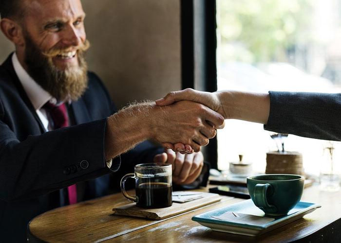 homem apertando a mão de alguém e fechando um contrato