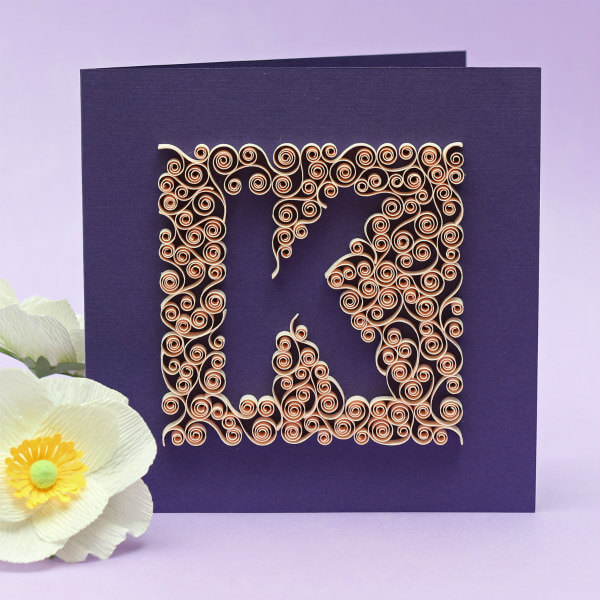 Letter K shape surrounded by ivory quilled scrolls on purple card