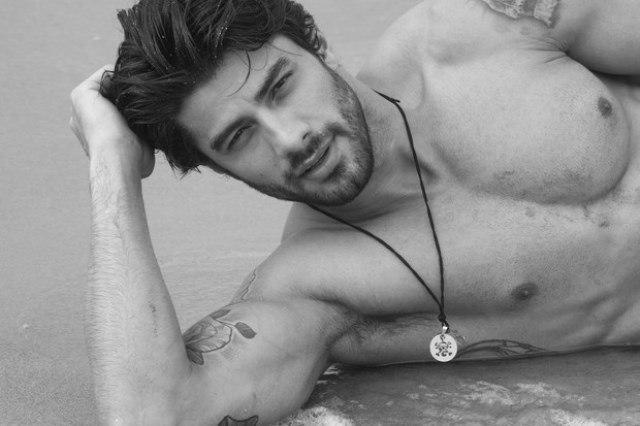 Foto de Renan Oliveira do BBB16 deitado na areia da praia