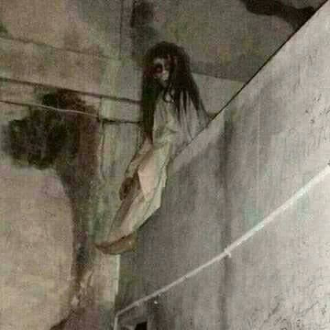 Pontianak demon sitting on top of a wall